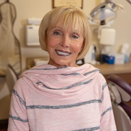 Woman in dental chair smiling after full mouth reconstruction